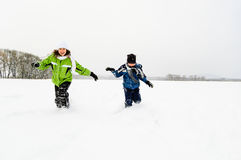 Kids running on snowy field Royalty Free Stock Images