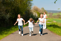 Kids running in spring, mother standing. Kids running down a path in spring, their mother standing in the background stock image
