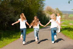 Kids running in spring, mother standing. Kids running down a path in spring, their mother standing in the background stock photos