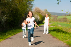 Kids running in spring, mother standing. Kids running down a path in spring, their mother standing in the background royalty free stock images