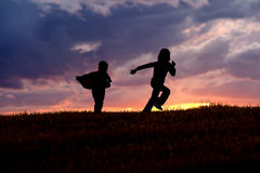 Kids running at sunset. Royalty Free Stock Photography