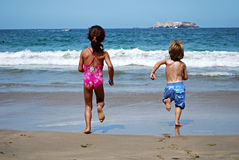 Kids running towards the sea Stock Image