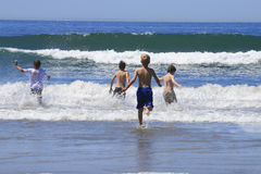 Kids running into waves Stock Photography