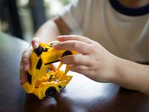 Close up of kids`s hand playing with a plastic toy car royalty free stock images