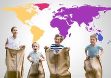 Kids in sack race in front of colorful world map Royalty Free Stock Images