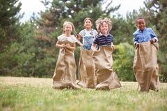 Kids at sack race. Kids having fun at sack race at the park stock photography