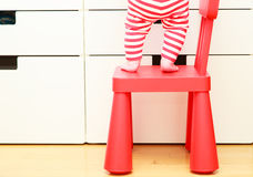 Kids safety concept- little girl climb on chair Royalty Free Stock Image