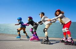 Kids in safety helmets rollerblading on the track Stock Photo