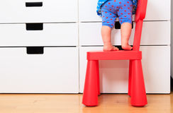 Kids safety - little girl climbing on baby chair Stock Images
