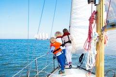 Kids sail on yacht in sea. Child sailing on boat. Little boy and girl in safe life jackets travel on ocean ship. Children enjoy yachting cruise. Summer Stock Photos