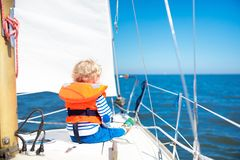 Kids sail on yacht in sea. Child sailing on boat. Little boy in safe life jackets travel on ocean ship. Children enjoy yachting cruise. Summer vacation for Royalty Free Stock Photos