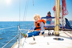 Kids sail on yacht in sea. Child sailing on boat. Little boy in safe life jackets travel on ocean ship. Children enjoy yachting cruise. Summer vacation for Stock Image