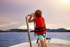 Kids sail on yacht in sea. Child sailing on boat. Little girl in safe life jackets travel on ocean ship. Children enjoy yachting cruise. Summer vacation for royalty free stock image