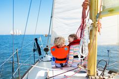 Kids sail on yacht in sea. Child sailing on boat. Little boy and girl in safe life jackets travel on ocean ship. Children enjoy yachting cruise. Summer Stock Photo