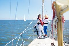 Kids sail on yacht in sea. Child sailing on boat. Little boy and girl in safe life jackets travel on ocean ship. Children enjoy yachting cruise. Summer Stock Photography