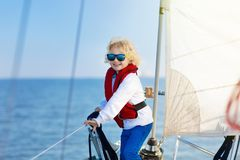 Kids sail on yacht in sea. Child sailing on boat. Little boy in safe life jackets travel on ocean ship. Children enjoy yachting cruise. Summer vacation for Stock Photos