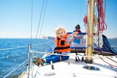 Kids sail on yacht in sea. Child sailing on boat. Little boy in safe life jackets travel on ocean ship. Children enjoy yachting cruise. Summer vacation for Royalty Free Stock Image