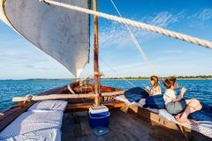 Kids sailing in dhow. Kids sailing in a traditional African dhow boat on sunset Stock Image