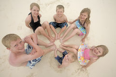 Kids in sand. Six children sitting in a circle in with their feet together in the sand Stock Photo