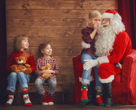 Kids and Santa Claus. Merry Christmas and Happy Holidays. Group of three kids and Santa Claus on wooden background. Kids have presents stock photography