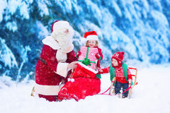 Kids and Santa Claus opening presents in snowy forest Stock Photography