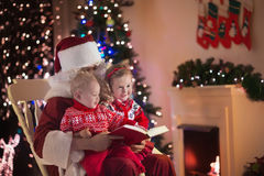 Kids and Santa at fire place on Christmas eve Stock Photo