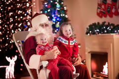 Kids and Santa at fire place on Christmas eve Royalty Free Stock Images