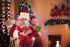 Kids and Santa at fire place on Christmas eve Stock Image