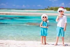 Kids in Santa hats at the beach Stock Photo