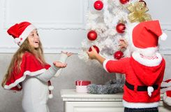 Kids in santa hats decorating christmas tree. Family tradition concept. Children decorating christmas tree together. Siblings busy decorating. Boy and girl stock photo