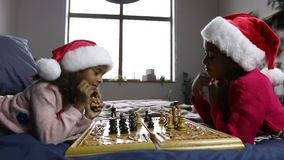 Kids in santa hats playing chess and thinking stock video footage