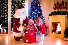 Kids and Santa opening Christmas presents Stock Image