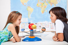 Kids with a scale model planetary system in science class. Kids with a scale model planetary system in geography science class discussing stock photos