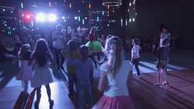 Kids on scene repeat dance moves after host actors in costumes in event room stock footage