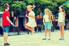 Kids in school age playing together with jumping rope Stock Photo