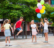 Kids in school age playing together with jumping rope Stock Photos