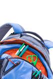 Kids school backpack with pens and scissors. Kids blue and orange school backpack with pens and scissors stowed in the pockets for a creative art class, close up Royalty Free Stock Images