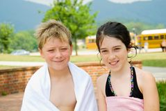 Kids/School Bus in Background. Boy and girl who have been swimming at camp.  School buses in the background--the fun is almost over and it will be back-to-school Royalty Free Stock Photos