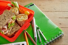 Kids school lunch box with ham sandwich. Rolex rolls and diced fresh vegetables open on a class notebook with pens, pencil and compass royalty free stock image
