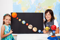 Kids in science class study the solar system. Kids in elementary school science class study the solar system - making a scale model of the planets stock photos