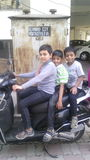 Kids on scooty. Image of three young brothers on scooty which show that they hav courage Royalty Free Stock Photography