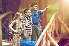 Kids scouts traveler with backpack hiking on bridge Stock Images