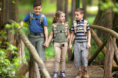 Kids scouts traveler with backpack hiking bridge in forest Stock Photo