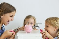 Kids with screwdriver, pliers and hammer by the pink pig piggy bank royalty free stock images