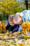 Kids searching amongst autumn leaves. Two happy young kids kneeling on the ground searching amongst fallen yellow autumn leaves in a park stock images