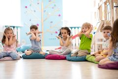 Kids seating on floor and show gestures making task. In daycare stock photo
