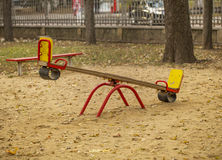 Kids seesaw on sandy playground in city park. Kids seesaw on sandy playground in autumn city park. Background: fence, car, trees Royalty Free Stock Photo