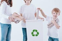 Kids segregating paper. Happy kids segregating paper waste into a white trashcan stock photo
