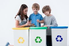 Kids segregating trash. Into different colored bins royalty free stock image