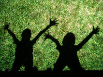 Kids shadows. In backyard green grass Stock Photography